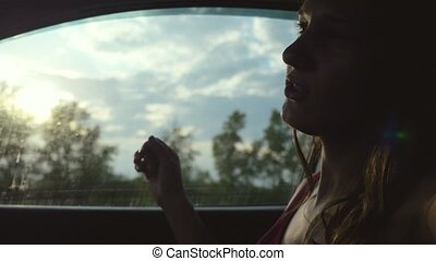 Happy young woman sitting in car passenger looking out...