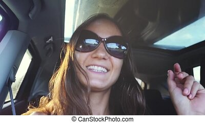 Cheerful young woman wears sunglasses sitting in car passenger and singing song in slow motion with beautiful sun lense flare effects on the background.