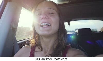 Joyful young woman sitting in car passenger enjoying rural...