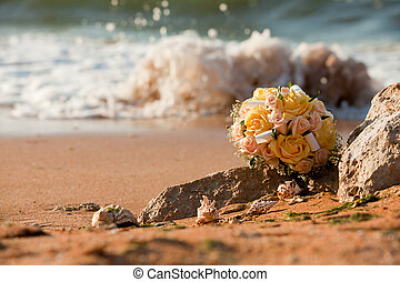 Bridal bouquet lies on the beach.