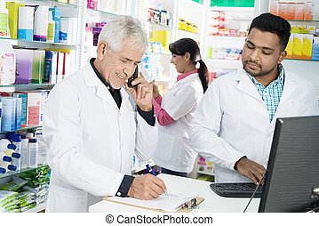 Chemist Taking Order On Phone While Colleagues Working In...