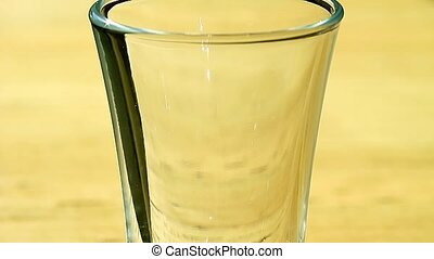 pouring liquor into a glass - pouring blue liquor into a...