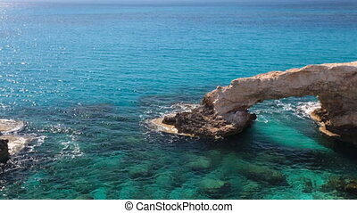 Rock and blue sea. Natural Bridge - Rock and blue sea in...