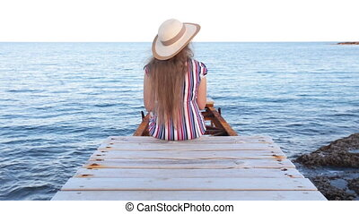 Young woman sitting on pier - Girl sitting on pier and...