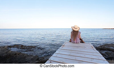 Young woman sitting on pier