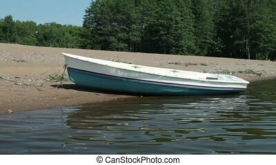 Rowingboat moored at shore Swaying on the wave, summer sunny...