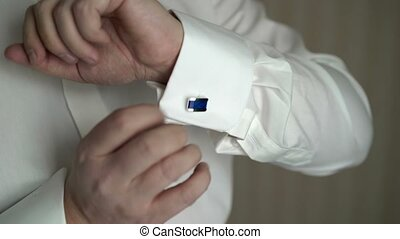 Man wears blue cufflinks - Unrecognizable young man wears...