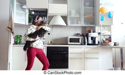 Happy young beautiful woman is dancing in kitchen with her...