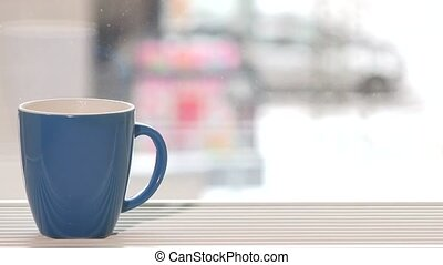 blue cup of coffee tea hot drink stand on window sill and...