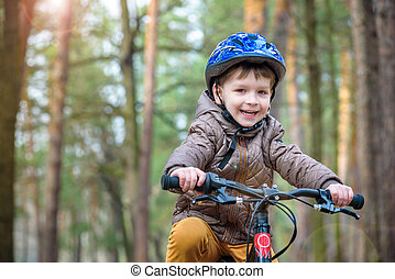 Happy kid boy of 3 or 5 years having fun in autumn forest...