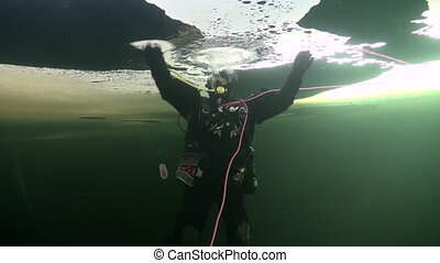 Diver underwter in ice of White Sea. Creative diving and...