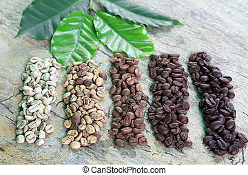 Coffee beans in different roast levels on rustic wooden...