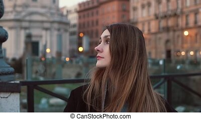 Portrait of woman standing in city centre and looking aside....
