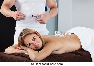 Smiling Woman Receiving Cupping Treatment On Back
