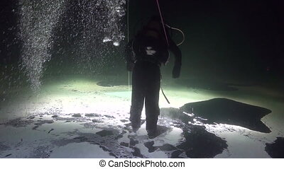 Diver goes on ice underwter of White Sea. Creative diving...