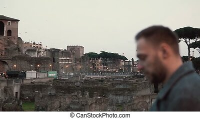 Handsome brunette man with a beard standing at the ruins in Rome, Italy, looking at map in his hands. Slow motion.