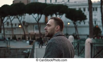 A handsome man considers sights in centre of Rome in Italy...