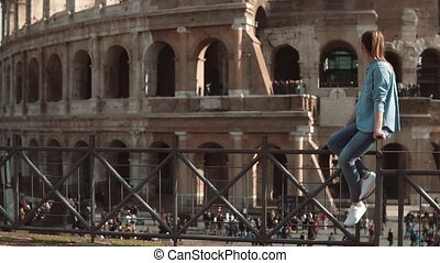 Woman sits on the fence looking at Colosseum in Rome, Italy...