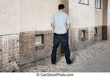 Man Peeing On The Wall Of A Building - Rear View Of A Man...