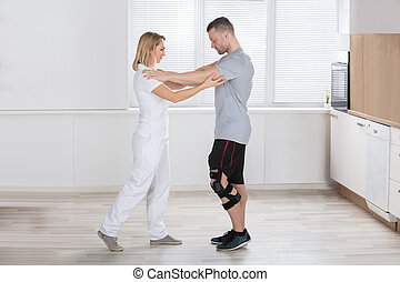 Physiotherapist Giving Treatment To Male Patient