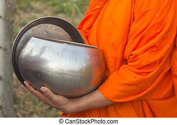 Thai monk with alms to a Buddhist monk on morning