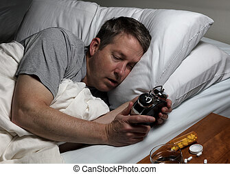 Mature man cannot fall asleep thus looking at time on alarm...