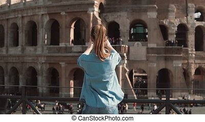 Tourist woman takes photos of the Colosseum and the arch of...