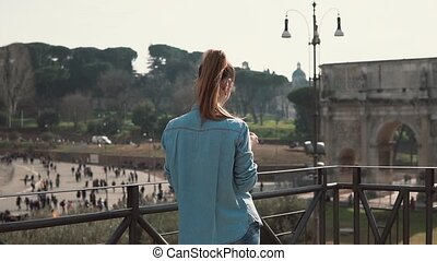 Tourist brunette woman takes photos of arch of Constantine...
