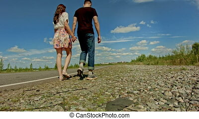 Rear view of male and female legs walking on summer countryside highway - traveling concept