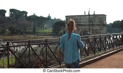 Woman walks down the street in Rome, Italy, takes photos of Colosseum, arch of Constantine with smartphone. Slow motion.