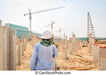 Surveyor engineer making measuring with optical equipment theodolite on blue sky background at construction site.