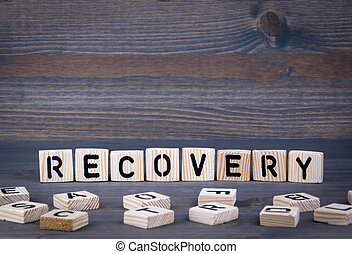 Recovery word written on wood block. Dark wood background...