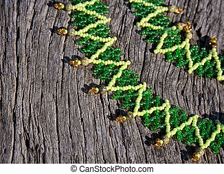 green bead-work lace on a wooden background. Soft selective...