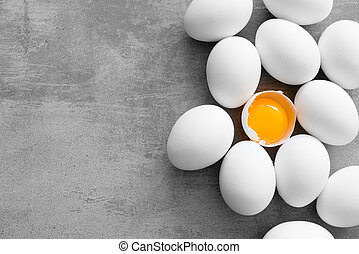 White eggs on a concrete table. One egg is cracked and you...