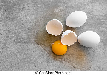 White eggs on a concrete table. One egg is broken and the...