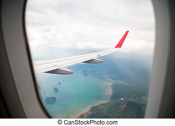 Island view through aircraft windows over the sea