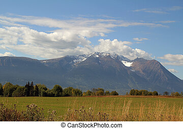 Mountain Field - farm field with snow capped mountains,...