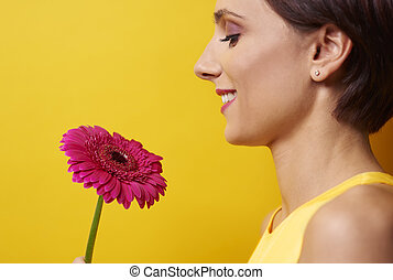 Profile view of woman holding flower