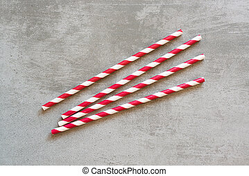 Red and white striped drinking straws on concrete background