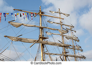 Masts and rigging of a sailing ship with flags, against blue...