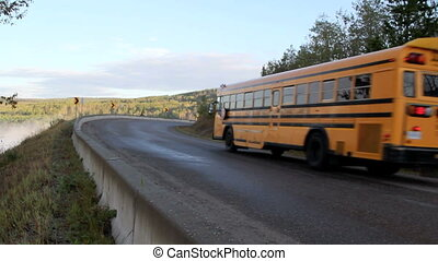School Bus - school bus climbing hill and going around a...