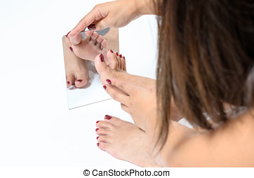 Woman admiring her painted toenails in a mirror after having...