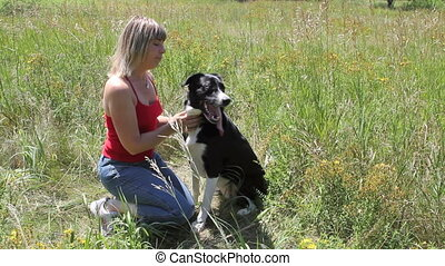 Lovin' - woman and her dog share affection in meadow