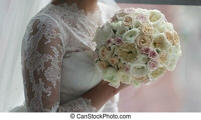 Young unrecognizable bride with flowers near window - Young...