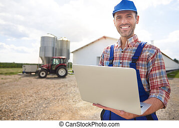 Farmer with laptop and his farm