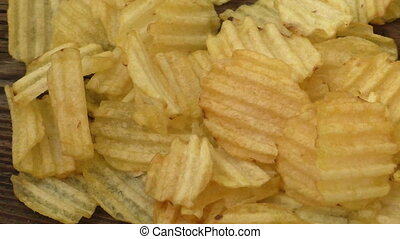 Rippled potato chips on a wooden background