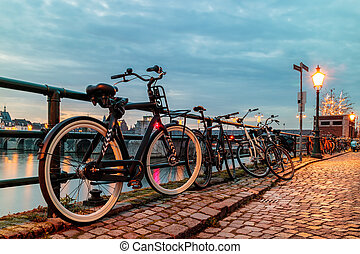 Evening view of parked bicycles alongside the Dutch river...