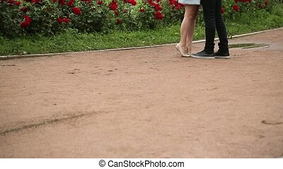 Young lovely couple kissing in park at summer day