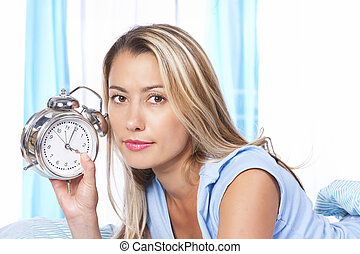 Woman with alarmclock - Woman holding alarm clock in her bed