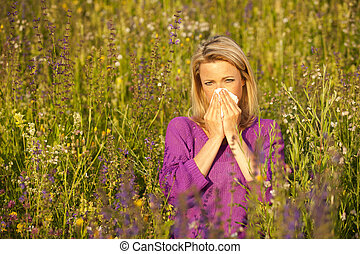 Attractive woman in a flower field with allergic symptoms...